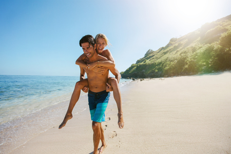 piggyback ride: Portrait of man carrying girlfriend on his back along the sea shore. Man giving piggyback ride to girlfriend on the beach.