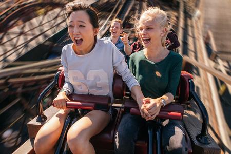 Выстрел из счастливых молодых людей, едущих на американских горках. Молодые женщины и мужчины с удовольствием на поездки в парке аттракционов. Фото со стока