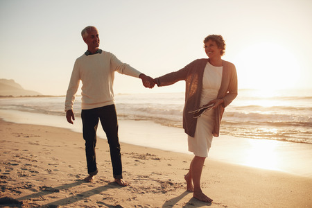 happy seniors: Full length outdoor shot of loving mature couple walking along the beach holding hands. Senior man and woman walking on the sea shore at sunset.