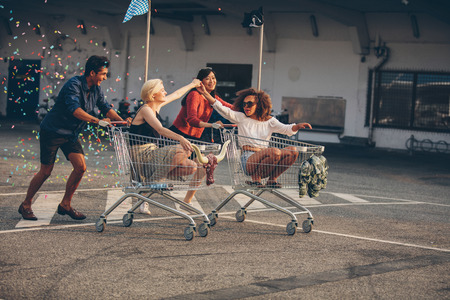 Young friends having fun on shopping carts. Multiracial young people racing on shopping cart.