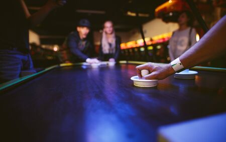 striker: Young friends playing air hockey game at amusement park, focus on hand of man holding striker. Stock Photo
