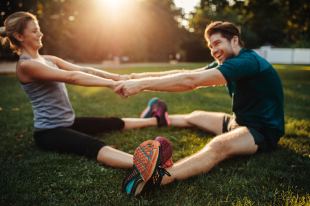 Young health couple doing stretching exercise and warm up in park. Man and woman sitting together holding hands and exercising.