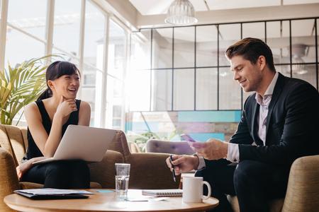 Plan de deux affaires réunion professionnelle dans le hall de bureau moderne. Femme travaillant sur ordinateur portable avec l'homme utilisant un téléphone mobile. Banque d'images - 66478413