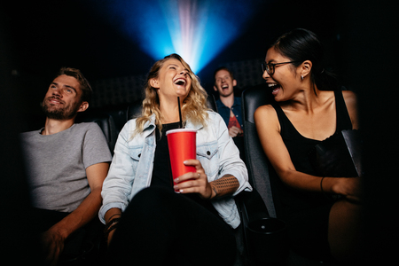 Young woman with friends in cinema hall watching movie. Group of people watching movie in theater and laughing.