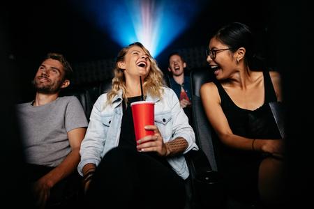Mujer joven con amigos en la sala de cine mirando la película. Grupo de personas viendo cine en el teatro y riendo.