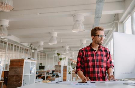 Colpo di giovani uomo d'affari in abiti casual nello spazio ufficio moderno business startup, lavorando su computer desktop.