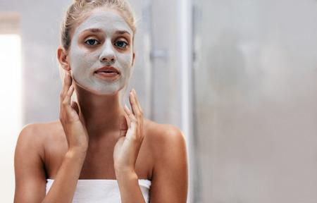 Close up disparo de mujer con máscara facial en el baño. Hermosa mujer haciendo tratamiento de belleza después del baño.