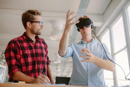 percepción: Tiro de dos hombres jóvenes de pruebas casco de realidad virtual. Los hombres de negocios discutir y probar las gafas de realidad virtual. Foto de archivo