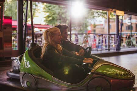 dashing: Happy young couple driving a bumper car at amusement park. Young man and woman riding bumper car at fairground.