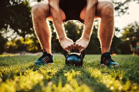 Bijgesneden opname van fit jonge man doen kettlebell training in het park, focus op handen houden ketel bel op gras. Stockfoto