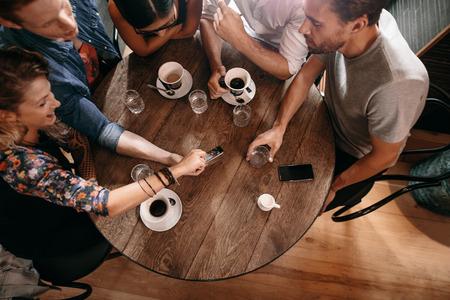 Bovenaanzicht van jongeren zitten rond een cafe tafel en kijkt naar de mobiele telefoon. Jonge mannen en vrouwen te kijken naar foto's op slimme telefoon.