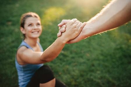 クローズ アップに立ち向かう女性を助ける人のショット。カップルが公園で運動の手に焦点を当てます。