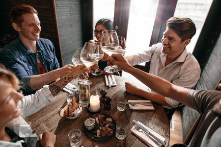 남자와 여자 레스토랑에서 와인을 즐기고의 그룹입니다. 카페에서 와인 토스트 한 젊은 친구.