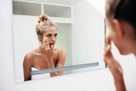 putting in: Reflection of a female in mirror rubbing cosmetic cream on her face. Female putting on moisturizer on her facial skin in bathroom. Stock Photo