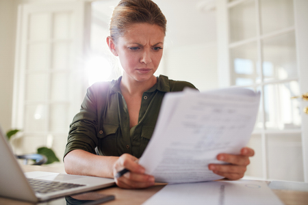 Portrait of young female sitting at table reading documents. Woman busy working at home office.