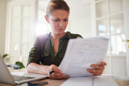soustředění: Portrét mladé ženy sedí u stolu čtení dokumentů. Žena pracuje v domácí kanceláři.