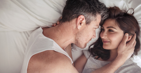 sexual intimacy: Overhead close up of young couple lying in bed together. Romantic couple in love looking at each other. Stock Photo