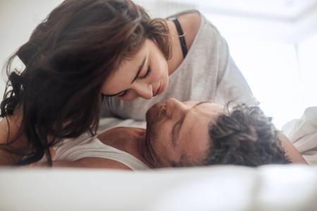 젊은 부부 함께 침대에 누워 애 무하는. 키스 및 껴 안고 관계에서 몇입니다.