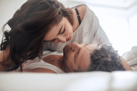 sexual foreplay: Young couple caressing lying in bed together. Couple in a relationship kissing and cuddling.