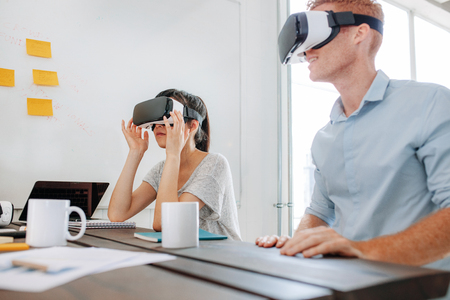 Young man and woman sitting at a table and using virtual reality goggles. Business team using virtual reality headset in office meeting. Stock Photo