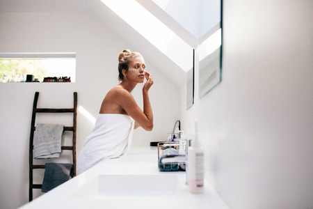 applying: Young woman wrapped in towel looking in the mirror and applying cream on her face. Female taking care of her face skin in bathroom after bath.