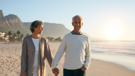 Outdoors shot of happy mature couple strolling on the beach. Senior man and senior woman taking a walk on the sea shore.