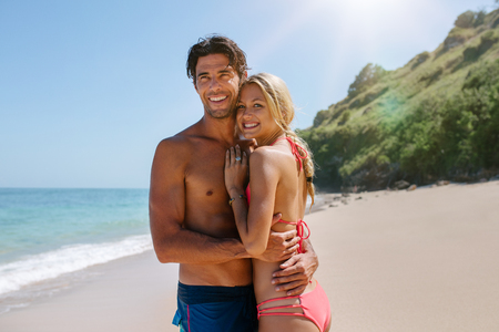 nature beauty: Loving couple in swimsuit embracing on the beach. Romantic young couple on sea shore  looking away and smiling. Stock Photo