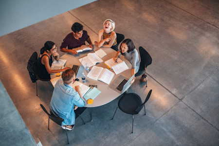 students group: Top view of group of students sitting together at table. University students doing group study and smiling. Stock Photo