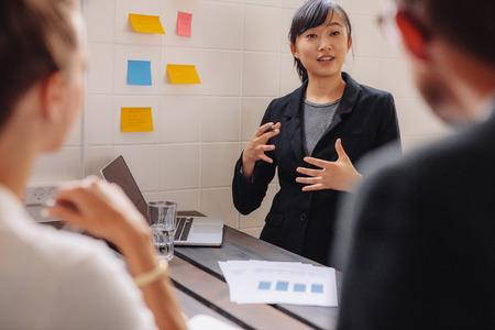 비즈니스 프레젠테이션을 선도하는 스티커 메모와 함께 벽에 의해 사업가 서. 회의실에서 프레젠테이션 중에 접착제 노트에 그녀의 아이디어를 넣어  스톡 콘텐츠