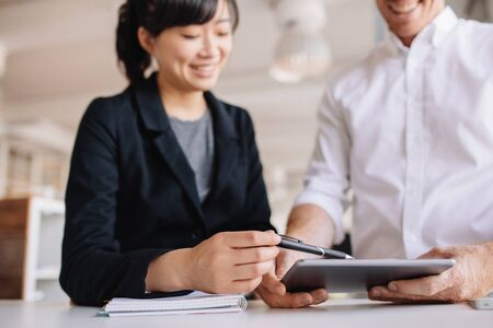 asian business man: Two young business people working together, with female executive pointing digital tablet. Businessman and businesswoman using touchscreen computer in office. Stock Photo
