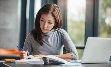 Shot of young woman taking down notes in diary. Female university student preparing note for the exam at library.
