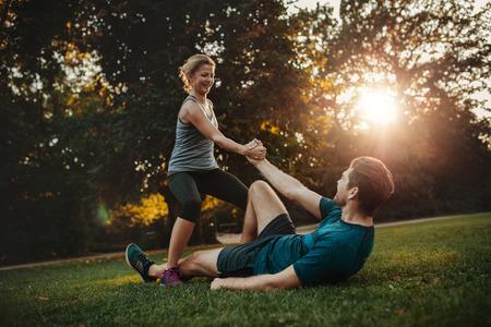Colpo di giovane donna aiutare l'uomo ad alzarsi da terra. Healthy giovane coppia al parco di esercitare insieme. Archivio Fotografico