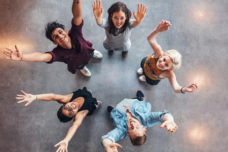 Bovenaanzicht van jonge studenten die samen staan omhoog te kijken naar camera met hun handen omhoog gevierd. Stockfoto