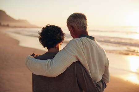 rear view: Rear view shot of a senior couple walking on the sea shore. Loving mature couple spending leisurely time on the beach at sunset. Stock Photo