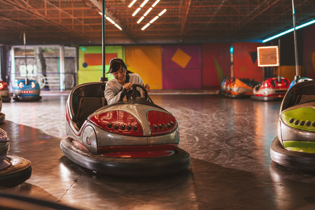 asian lady: Happy young woman driving a bumper car at amusement park