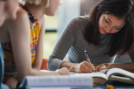 Young woman taking notes from books for her study. Students sitting at table with books preparing school assignment. Stock Photo