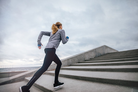 Outdoor shot of fit young woman running on steps. Runner exercising on stairs in morning.