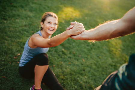 Man helping her girlfriend with focus on hands. Couple exercising in park. Stock Photo