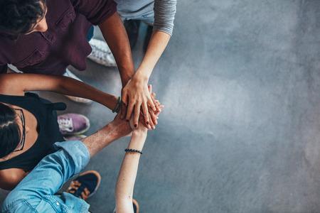 그들의 손을 함께 넣어 젊은 사람들의 그룹의 상위 뷰 이미지. 단결을 보여주는 손의 스택과 함께 친구. 스톡 콘텐츠