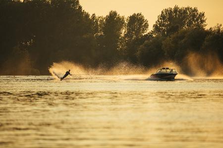 Buiten schot van de man wakeboarden op meer bij zonsondergang. Waterskiën op het meer achter een boot.