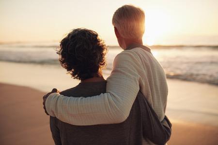 놀라운 일몰을보고 은퇴 한 부부의 후면보기 샷. 해변에서 함께 서 수석 남자와 여자. 스톡 콘텐츠