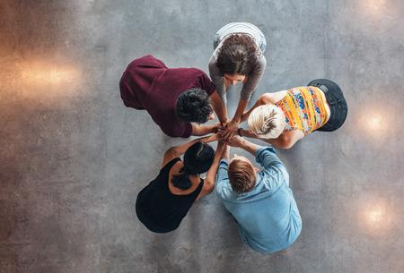 Bovenaanzicht van de groep van jonge mensen zetten hun handen in elkaar. Jonge studenten staan in een cirkel maken stapel handen waaruit blijkt succes.