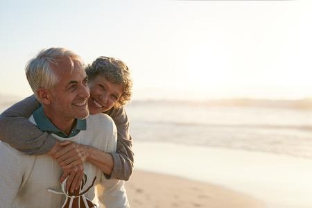 ビーチで彼の妻によって受け入れられている幸せな成熟した男の肖像画。シニア カップル海の海岸で楽しんで。