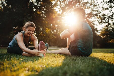 couple exercising: Caucasian couple doing their stretches in park. Fit young man and woman exercising in morning.