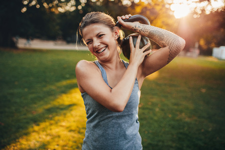 sportsperson: Portrait of happy young woman with kettlebell weights on her shoulder in the park.