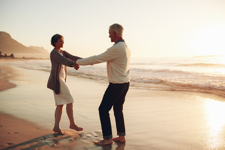 로맨틱 수석 몇 손을 잡고 해변에서 하루를 즐기고의 전체 길이 샷. 해변에서 자신을 즐기는 성숙한 커플.