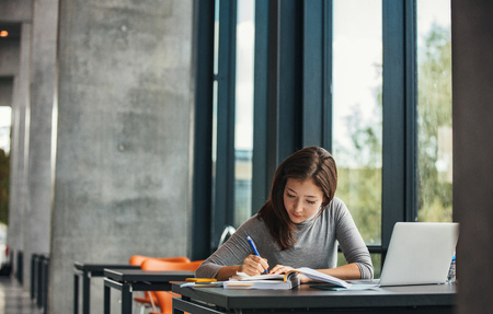 Shot of young asian female student sitting at table and writing on notebook. Young female student studying in library. 版權商用圖片 - 67398514