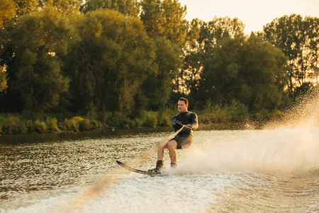 sportsperson: Outdoor shot of man wakeboarding on lake at sunset. Water skiing on lake behind a boat.