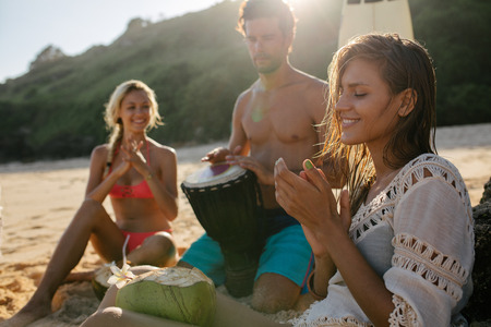 young women: Young woman enjoying holidays with her friends on the beach. Women clapping and man playing dumbek.