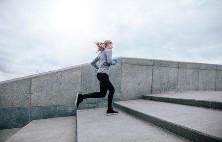 Seitenansicht in voller Länge Schuss von fit junge Frau läuft bis Treppen. Fitness weiblich am Morgen Training. Standard-Bild - 67421320